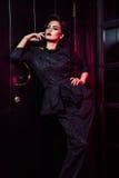 Retrato del modelo de moda hermoso en vestido negro clásico, maquillaje y peinado cerca de la situación y de la presentación oscu Imágenes de archivo libres de regalías