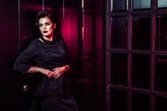Retrato del modelo de moda hermoso en vestido negro clásico, maquillaje y peinado cerca de la situación y de la presentación oscu Fotografía de archivo