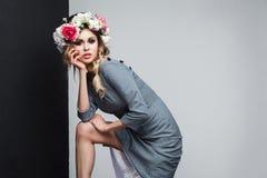 Retrato del modelo de moda sensual hermoso en vestido gris con el maquillaje y las flores principales que plantean y que miran la foto de archivo libre de regalías