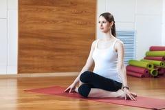 Retrato del modelo embarazada joven sonriente de la aptitud en la ropa de deportes que hace el entrenamiento de la yoga o de los  Imagen de archivo libre de regalías