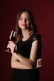 Retrato del modelo en vestido negro con el vino Cierre para arriba Fondo rojo oscuro Fotos de archivo