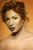 Retrato del modelo femenino de la moda con maquillaje de oro imagenes de archivo