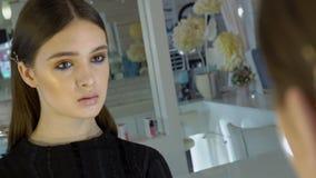 Retrato del modelo femenino joven que está mirando su reflexión en el espejo en estudio metrajes