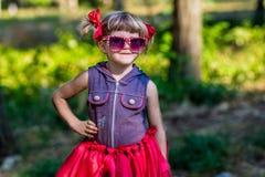Retrato del modelo hermoso de la niña en gafas de sol en arcos en un parque Imagen de archivo