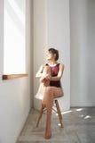 Retrato del modelo hermoso feliz joven en el traje de baño que se sienta en la silla que mira la ventana que disfruta de sunlight imagenes de archivo