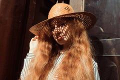 Retrato del modelo pelirrojo joven en sombrero de paja con la sombra en h Fotografía de archivo libre de regalías