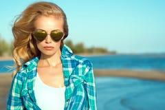 Retrato del modelo rubio bronceado atractivo magnífico joven que lleva las gafas de sol en forma de corazón duplicadas y la camis Foto de archivo libre de regalías