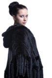 Mujer en el abrigo de pieles negro de lujo del color que mira detrás   fotografía de archivo