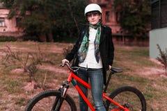 Retrato del montar a caballo joven feliz del ciclista en parque Fotografía de archivo