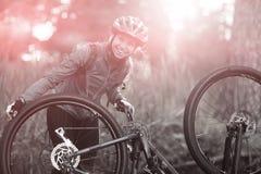Retrato del motorista femenino que repara la bici de montaña Fotos de archivo