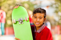 Retrato del muchacho árabe con el monopatín verde Fotos de archivo