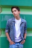 Retrato del muchacho adolescente atractivo hermoso que permanece al aire libre cerca de la pared verde vieja Foto de archivo libre de regalías
