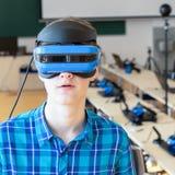 Retrato del muchacho adolescente de la edad que lleva las auriculares de VR y que mira la cámara Imágenes de archivo libres de regalías