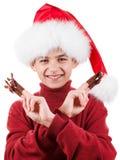 Retrato del muchacho adolescente feliz en el sombrero de Papá Noel con el juguete de los ciervos para arriba aislado en blanco Fotografía de archivo