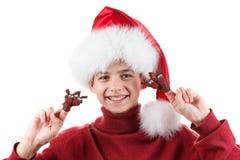 Retrato del muchacho adolescente feliz en el sombrero de Papá Noel con el juguete de los ciervos para arriba aislado en blanco Imágenes de archivo libres de regalías