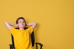 Retrato del muchacho adolescente feliz en la camiseta amarilla que mira hacia arriba adentro Foto de archivo