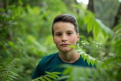 Retrato del muchacho adolescente joven en bosque Imagen de archivo libre de regalías