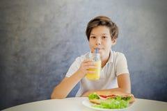 Retrato del muchacho adolescente lindo que desayuna en casa Fotografía de archivo