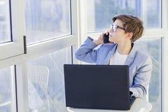 Retrato del muchacho adolescente que habla sobre el teléfono móvil y que usa el ordenador portátil Fotos de archivo libres de regalías
