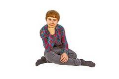 Retrato del muchacho adolescente que se sienta en el piso en estudio Imagenes de archivo