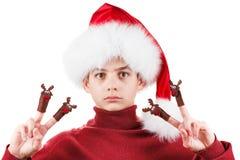 Retrato del muchacho adolescente serio en el sombrero de Papá Noel con el juguete de los ciervos para arriba aislado en blanco Fotos de archivo libres de regalías