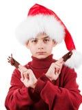 Retrato del muchacho adolescente serio en el sombrero de Papá Noel con el juguete de los ciervos para arriba aislado en blanco Imagenes de archivo