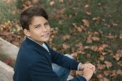 Retrato del muchacho adolescente sonriente de los jóvenes que mira la cámara con un joyf Foto de archivo libre de regalías