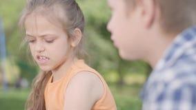 Retrato del muchacho adorable y de la muchacha que se sientan en el parque, hablando y divirtiéndose Un par de niños felices dive almacen de video