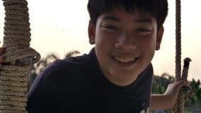 Retrato del muchacho asiático del niño que juega el oscilación con la llamarada de la puesta del sol en casa, adolescencia de la  almacen de video