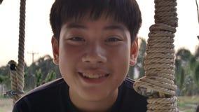 Retrato del muchacho asiático del niño que juega el oscilación con la llamarada de la puesta del sol en casa, adolescencia de la  metrajes