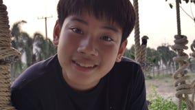 Retrato del muchacho asiático del niño que juega el oscilación con la llamarada de la puesta del sol en casa, adolescencia de la  almacen de metraje de vídeo