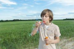 Retrato del muchacho caucásico del adolescente con las burbujas de jabón flotantes en el camino polvoriento del campo de granja d Imágenes de archivo libres de regalías