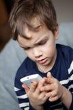 Retrato del muchacho con el teléfono móvil Fotografía de archivo
