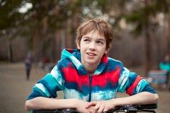 Retrato del muchacho con la bicicleta en parque Fotografía de archivo