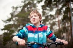 Retrato del muchacho con la bicicleta en parque Imagen de archivo libre de regalías