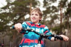 Retrato del muchacho con la bicicleta en parque Imagen de archivo