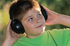 Retrato del muchacho con los auriculares al aire libre Imagen de archivo libre de regalías