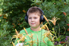 Retrato del muchacho con los auriculares alrededor del daylily Imagenes de archivo