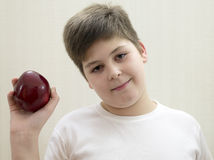 Retrato del muchacho con una manzana roja en la mano Imagen de archivo