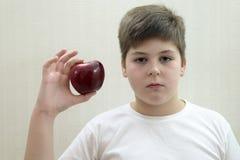 Retrato del muchacho con una manzana roja en la mano Imágenes de archivo libres de regalías