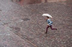 Retrato del muchacho corriente con el paraguas en lugar de los adoquines en la ciudad Foto de archivo libre de regalías