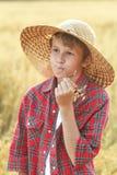 Retrato del muchacho de granja adolescente en el sombrero de ala ancha que mastica la paja de los oídos del cereal de la avena Imagenes de archivo