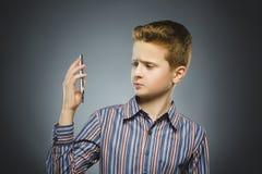 Retrato del muchacho de la ofensa con el móvil o el teléfono celular Emoción humana negativa Fotografía de archivo libre de regalías