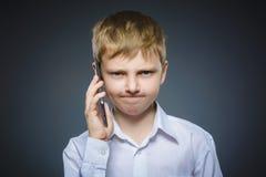 Retrato del muchacho de la ofensa con el móvil o el teléfono celular Emoción humana negativa Fotos de archivo libres de regalías