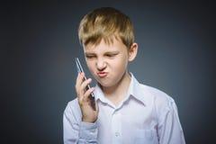 Retrato del muchacho de la ofensa con el móvil o el teléfono celular Emoción humana negativa Imagen de archivo libre de regalías
