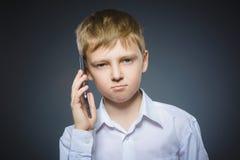 Retrato del muchacho de la ofensa con el móvil o el teléfono celular Emoción humana negativa Fotos de archivo
