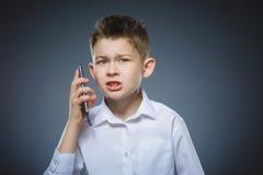 Retrato del muchacho de la ofensa con el móvil o el teléfono celular Emoción humana negativa foto de archivo