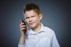 Retrato del muchacho de la ofensa con el móvil o el teléfono celular Emoción humana negativa Imagenes de archivo