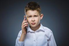 Retrato del muchacho de la ofensa con el móvil o el teléfono celular Emoción humana negativa Imagen de archivo