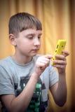 Retrato del muchacho del adolescente con el teléfono móvil en una mano Foto de archivo